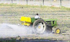 Farmer spraying isecticed on a field. Farmer driving a tractor and preparing a field for the season Royalty Free Stock Image