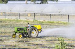 Farmer spraying isecticed on a field. Farmer driving a tractor and preparing a field for the season Royalty Free Stock Photo