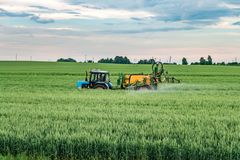 Farmer spraying wheat field with tractor sprayer at spring season.  royalty free stock photography