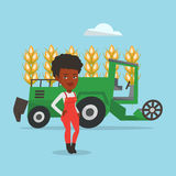 Farmer standing with combine on background. African-american farmer standing on the background of combine harvesting wheat in field. Combine harvesting wheat Stock Images