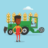 Farmer standing with combine on background. African-american farmer standing on the background of combine harvesting wheat in field. Combine harvesting wheat Royalty Free Stock Photo