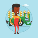 Farmer standing with combine on background. African farmer standing on the background of combine harvester working in field. Farmer and combine harvester Stock Photo