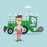 Farmer standing with combine on background. Caucasian farmer standing on the background of combine harvester working in wheat field. Farmer and combine Royalty Free Stock Photography