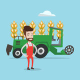 Farmer standing with combine on background. A hipster farmer with the beard standing on the background of combine working in wheat field. Combine harvesting Stock Image