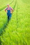 Farmer Standing In A Field. Farmer standing in a green cereal field Stock Photo