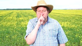 Farmer standing in field and making silence gesture on a sunny day.  stock video footage
