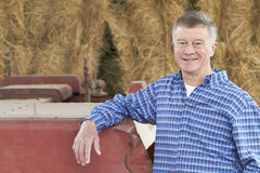 Farmer Standing In Front Of Bales And Old Farm Equipment Stock Image