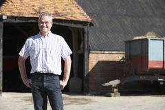 Farmer Standing In Front Of Farm Buildings Royalty Free Stock Photography