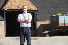 Farmer Standing In Front Of Farm Buildings Stock Image