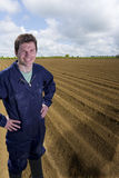 Farmer standing with hands on hips in ploughed field Royalty Free Stock Photo