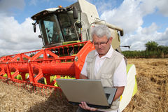 Farmer standing by harvester Stock Image
