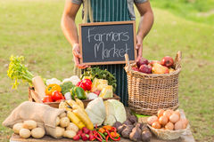 Farmer standing at his stall and holding chalkboard Royalty Free Stock Photography