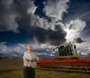 Farmer standing next to combine harvester in wheat field Royalty Free Stock Photos