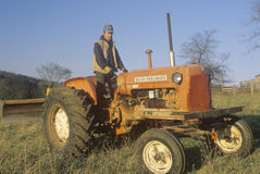 Farmer standing on tractor Royalty Free Stock Images