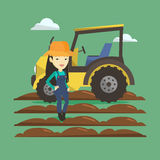 Farmer standing with tractor on background. Stock Images