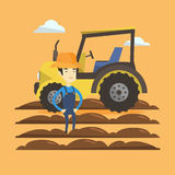Farmer standing with tractor on background. Stock Image