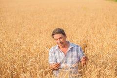 Farmer standing in a wheat field Stock Photo