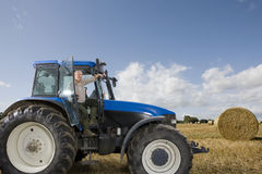 Farmer stepping down from tractor in hay field Stock Image