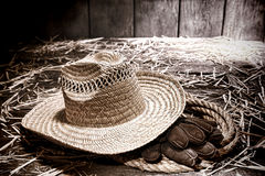 Farmer Straw Hat on Gloves in Rope at Old Hay Barn Stock Photo