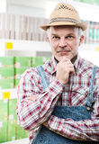 Farmer at supermarket with hand on chin Stock Photo