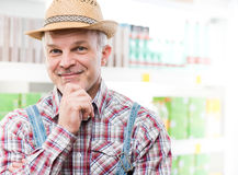 Farmer at supermarket with hand on chin Stock Images