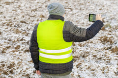 Farmer with tablet PC filmed plowed,frozen field with snow Royalty Free Stock Photo