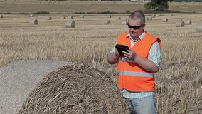 Farmer with tablet PC near hay bales on field in summer stock video footage