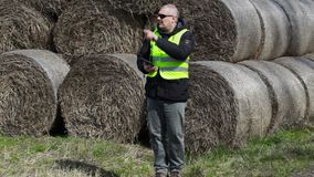 Farmer with tablet PC numbering the hay bales stock footage