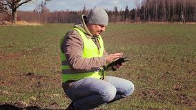 Farmer with tablet PC on the sown field in the spring stock video