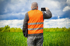Farmer take pictures on smart phone near the green cereal field Royalty Free Stock Image