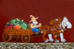 Farmer taking produce to market. Painting on wall depicting a caricature of famer taking a horse drawn wagon of vegetables to market Royalty Free Stock Images