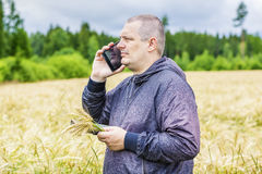 Farmer talking on cell phone near cereal field Stock Image