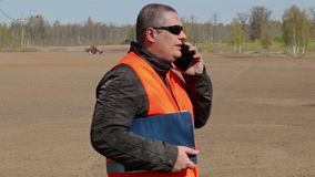 Farmer talking on smart phone at the field where the tractor harrow the ground stock video footage