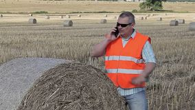Farmer talking on smartphone near hay bales stock video footage