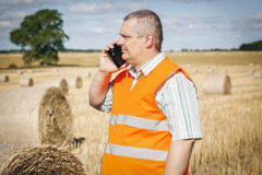 Farmer talking on smartphone near hay bales Stock Photography