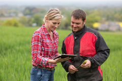 Farmer and technician working together with electronics Royalty Free Stock Images