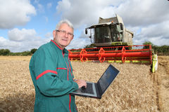 Farmer and technology. Farmer wih laptop computer in wheat field Royalty Free Stock Photography