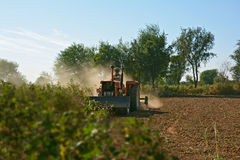 A farmer tilling soil for seedbed preparation with a Rotavator 'Rotary tiller' machine Royalty Free Stock Photos