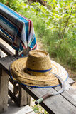 Farmer tools. Farmer hat, tool and cloth on wooden bench with green background Royalty Free Stock Image