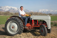 Farmer on tractor. Senior aged man driving on a small farm tractor Royalty Free Stock Images