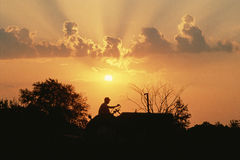 Farmer on Tractor. Silhouetted farmer on a tractor at sunset Stock Photo