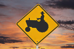 Farmer Tractor Crossing Sign with Sunrise Stock Photo