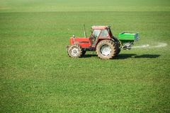 Farmer in tractor fertilizing wheat field at spring with npk. Agricultural activity Royalty Free Stock Image