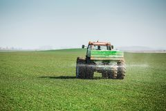 Farmer in tractor fertilizing wheat field at spring with npk. Agricultural activity Stock Image