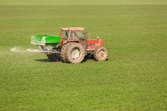 Farmer in tractor fertilizing wheat field at spring with npk. Agricultural activity Stock Photos