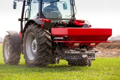 Farmer in tractor fertilizing wheat field at spring with npk stock images