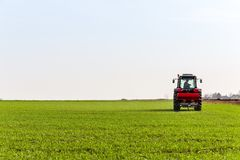 Farmer in tractor fertilizing wheat field at spring with npk stock photos