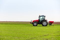 Farmer in tractor fertilizing wheat field at spring with npk royalty free stock images