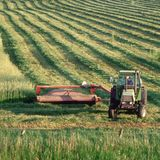 Farmer on tractor in field. Farmer on tractor cutting hay in farm field in Town of Sheboygan, Wisconsin in the united states of america part of the agricultural stock photos