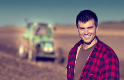 Farmer with tractor on field. Portrait of young handsome farmer on farmland. Tractor working in background Stock Images